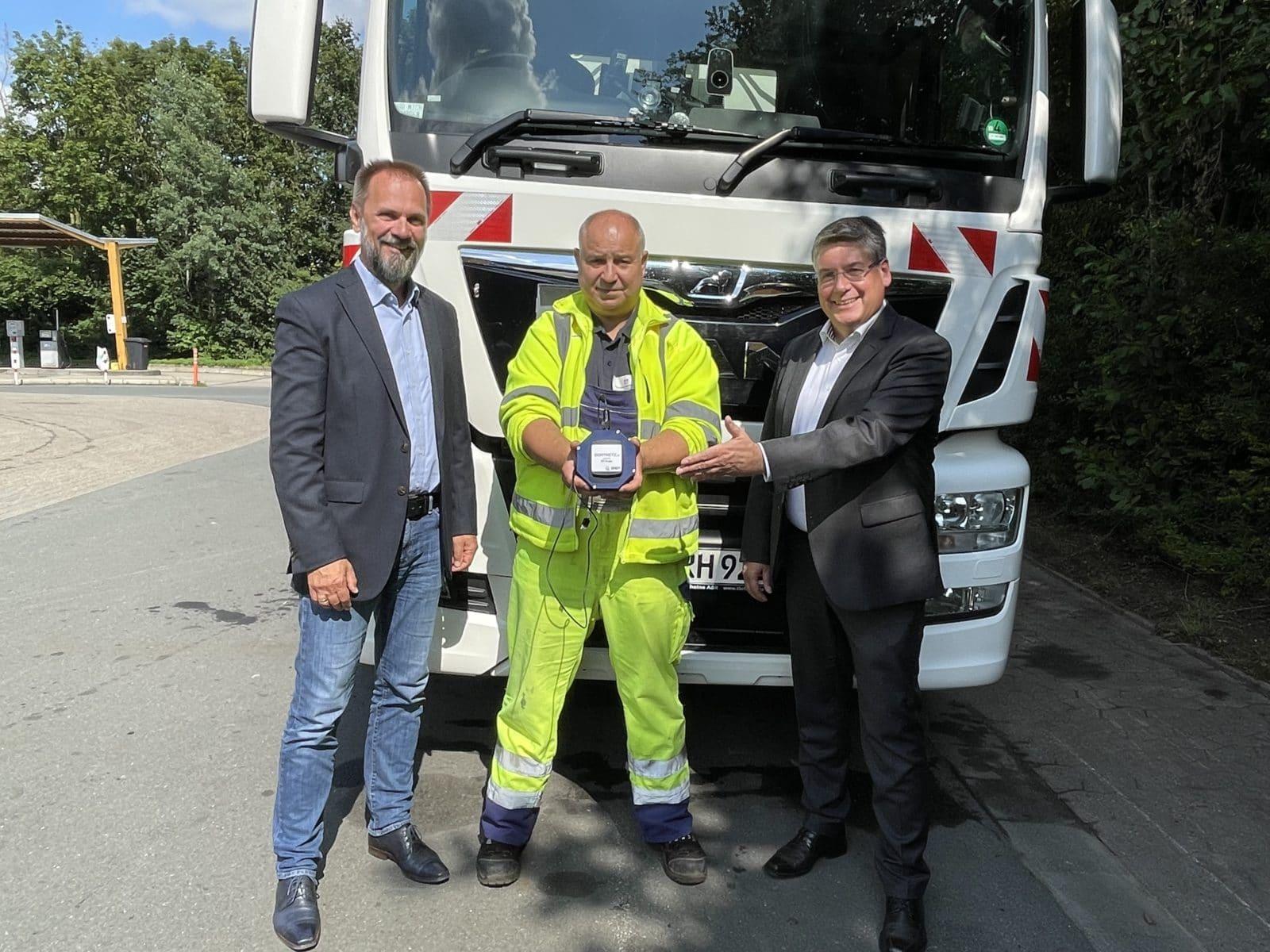 Helmut Neumann und Frédéric Dildei von der STF Gruppe mit einem Müllwagen-Fahrer der Stadt Rheine und der Mobilfunkmessbox